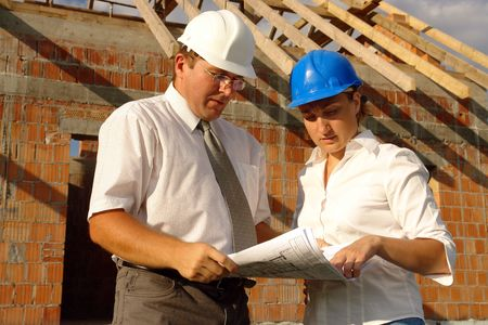 Female and male building engineers wearing helmets discussing building plans standing over unfinished brick house with wooden roof structure photo