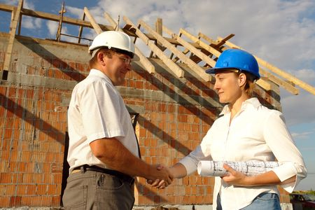 Female investor and male building engineer shaking hands standing over unfinished brick  with wooden roof structure