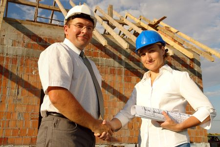Female investor and male building engineer shaking hands standing over unfinished brick house with wooden roof structure photo