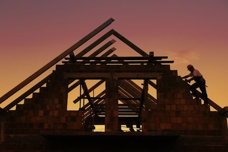 rafter: Construction worker working with house wooden roof against sunset sky