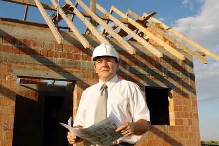 Building engineer wearing white helmet discussing holding building plans standing over unfinished brick house with wooden roof structure