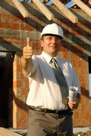 Ingeniero civil llevaba casco blanco rollo de la celebraci�n de los planes de construcci�n que muestra el pulgar en se�al de la casa sin terminar  Foto de archivo - 3497106