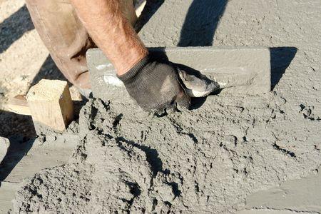 vijzel: Close-up van de mason hand verspreiding van concrete mix met truweel in Stichting bekisting  Stockfoto