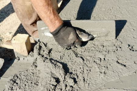 cement: Closeup of masons hand spreading concrete mix with trowel in foundation shuttering