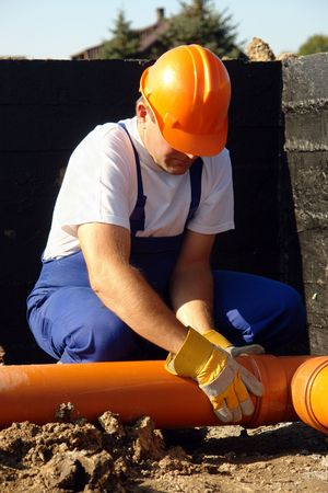 fixer: Plumber assembling pvc sewage pipes in  foundation Stock Photo