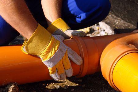 Close-up van de loodgieter handen montage pvc afvalwater pijpen in huis foundation