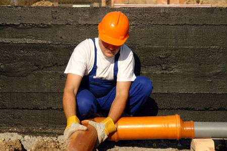 Plumber assembling pvc sewage pipes in  foundation Stock Photo