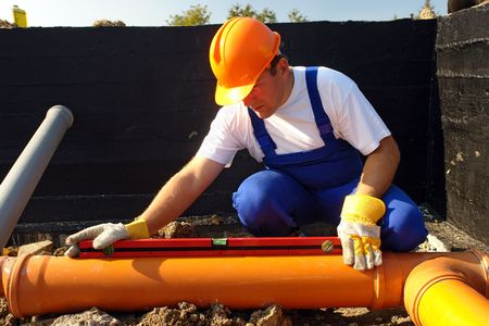 Plumber measuring slope of assembled sewage pipes using spirit level Stock Photo
