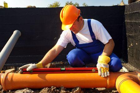 fixer: Plumber measuring slope of assembled sewage pipes using spirit level Stock Photo