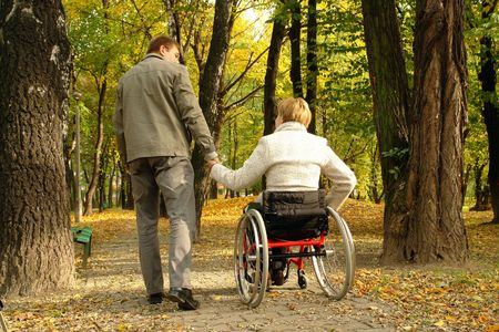 taking a wife: Husband and handicapped wife taking stroll in park alley in fall time Stock Photo