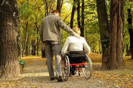 disable: Husband and handicapped wife taking stroll in park alley in fall time Stock Photo