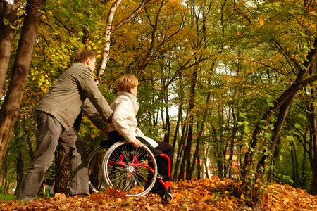 handicapped person: Husband and handicapped wife taking stroll in park alley in fall time Stock Photo