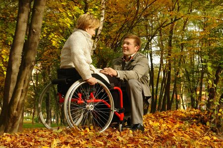 healthcare facilities: Husband and handicapped wife spending time together in park in fall time Stock Photo