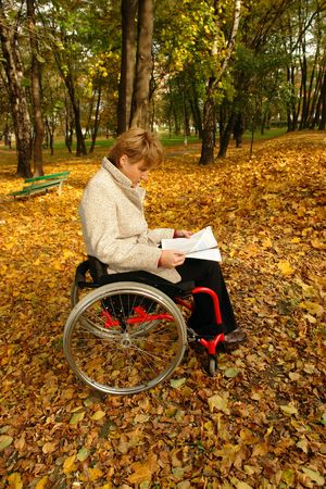 health facilities: Woman on wheelchair reading a magazine in the park in fall time Stock Photo