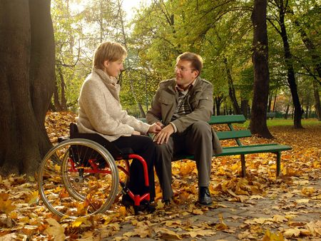 Husband and handicapped wife spending time together in park in fall time Stock Photo