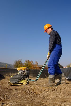 compacting: Construction worker compacting soil in house foundation using compactor Stock Photo