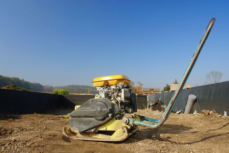 compacting: Soil compacting machine inside a house foundation