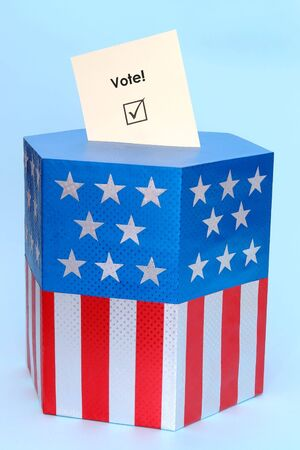 Yellow voting card half-inserted into ballot box decorated with american flag star and stripe colors over blue background Stock Photo - 3800234