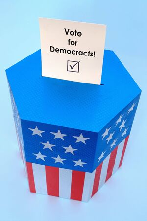 Yellow voting card with Vote for Democracts slogan half-inserted into ballot box decorated with american flag star and stripe colors over blue background Stock Photo - 3800233