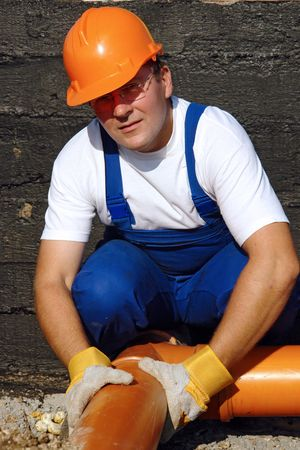 fixer: Plumber assembling pvc sewage pipes in house foundation Stock Photo