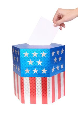 Hand casting vote into ballot box decorated with american flag star and stripe colors over white background Stock Photo - 3804956
