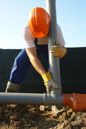 fitter: Plumber assembling pvc sewage pipes in house foundation Stock Photo