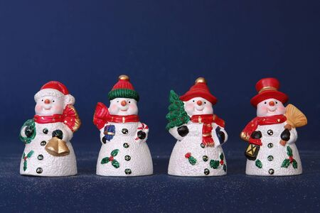Four snowmen in red hats over dark blue background Stock Photo - 3832832