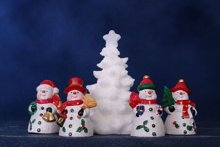 White xmas tree surrounded by four red hat snowmen over dark blue background Stock Photo - 3832831