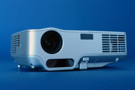 Silver multimedia projector shot over blue background Stock Photo - 3844953