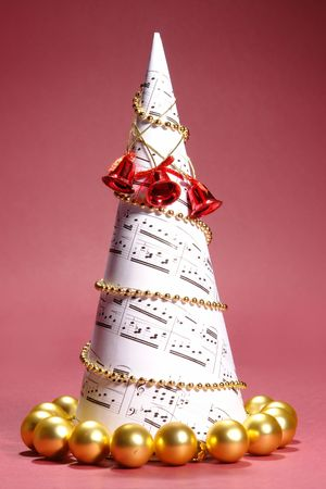 Paper christmas tree with carol notes over red background photo