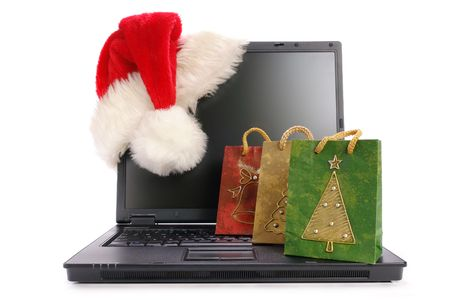 Black open laptop with red santa claus hat put on lcd corner and christmas shopping bags - isolated on white