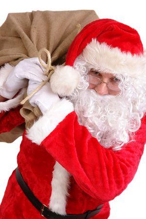 Santa Claus carrying big sack on his shoulder full of christmas presents photo