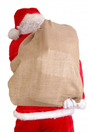 Santa Claus carrying big sack on his back full of christmas presents photo
