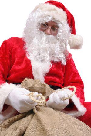 sackful: Santa Claus tying up big jute sack full of christmas presents over white