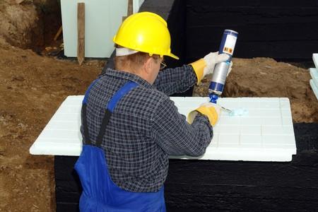 fixed: Trabajador de la construcci�n la aplicaci�n de pegamento en el aislamiento t�rmico de espuma de poliestireno paneles se fijar�n a paredes de la casa fundaci�n Foto de archivo