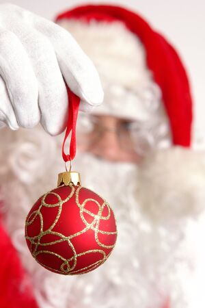 Closeup of Santa Claus holding red christmas ball photo