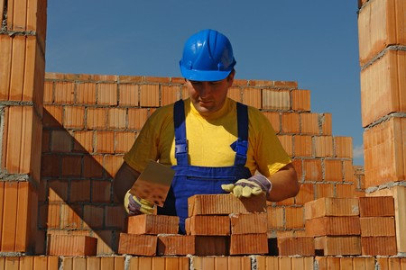 Mason in blue helmet building house wall in bricks