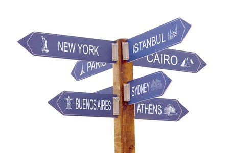 Wooden signpost indicating seven world famous cities over white