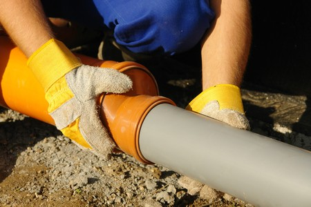 Closeup of plumbers hands assembling pvc sewage pipes in house foundation