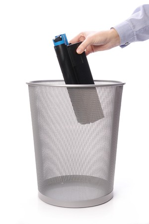 Female hand throwing used laser printer cartridge into metal trash bin over white