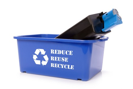 Used laser printer cartridge in blue recycle bin over white