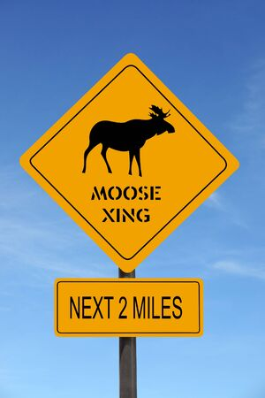 Moose Xing warning roadsign over blue sky Stock Photo
