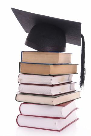 Black graduation cap on pile of books over white                 photo