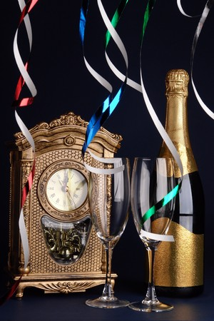 Table clock showing midnight, streamers, bottle of champagne and two glasses over dark blue background Stock Photo - 4007890
