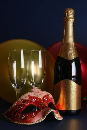 Venetian mask, bottle of champagne, two glasses and party balloons over dark blue background Stock Photo - 4007889