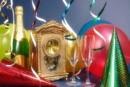Table clock showing midnight, party hats, streamers, balloons, bottle of champagne and two glasses photo