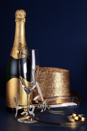 Bottle of champagne, two glasses and golden party hat