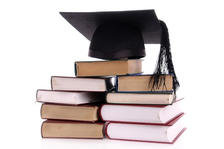 Black graduation cap on pile of books over white