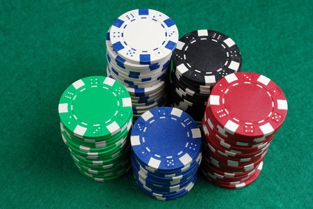 fichas de casino: Los montones de fichas de casino en un mantel verde