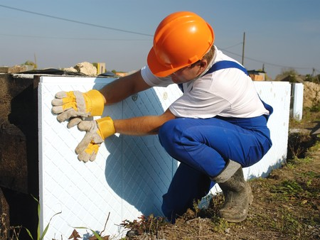 Construction worker fitting styrofoam thermal insulation panels to house foundation walls Stock Photo